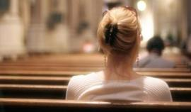 This photograph is taken from the back pew and shows the back of a woman's head, a woman who is also sitting in the back.  In the foreground is the blurred scene of a service in progress.